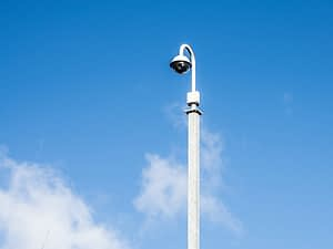PTZ CCTV Security Camera on Post against Blue Sky with Clouds